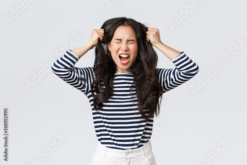 Lifestyle, people emotions and casual concept. Pissed-off mad and angry asian young woman tossing hair, pulling it from head with screams and closed eyes, standing bothered white background