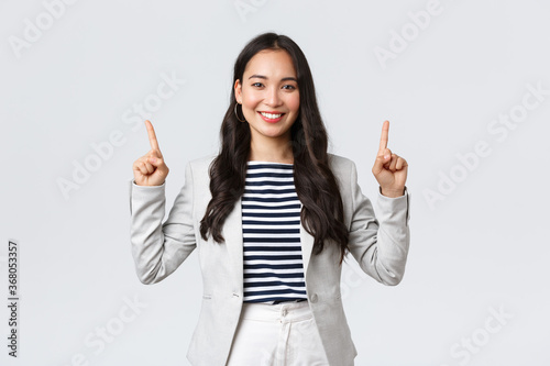 Business, finance and employment, female successful entrepreneurs concept. Successful confident smiling asian businesswoman pointing fingers up, real estate worker showing perfect proposal