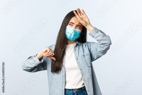 Social distancing lifestyle, covid-19 pandemic everyday life concept. Asian girl feeling bad, showing thumb-down as touching hot forehead, have high fever, wear medical mask, catch coronavirus