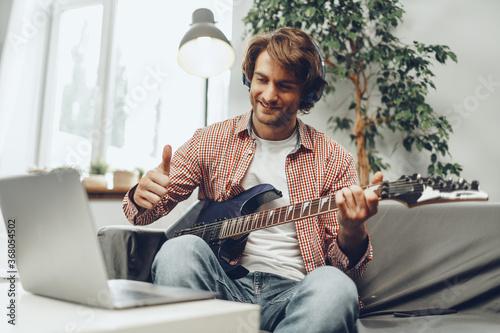 Fototapeta Man playing electric guitar and recording music into laptop