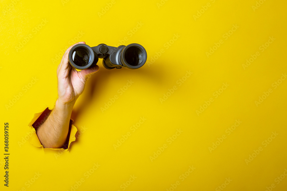 Fototapeta Female hand holds black binoculars on a yellow background. Looking through binoculars, journey, find and search concept