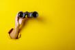 Leinwandbild Motiv Female hand holds black binoculars on a yellow background. Looking through binoculars, journey, find and search concept