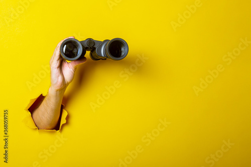 Obraz na plátně Female hand holds black binoculars on a yellow background