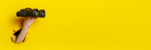 Female Hand Holds Black Binoculars On Yellow Background, Travel, Find And Search Concept. Banner.