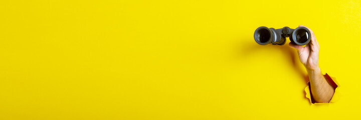 Female hand holds black binoculars on yellow background, travel, find and search concept. Banner