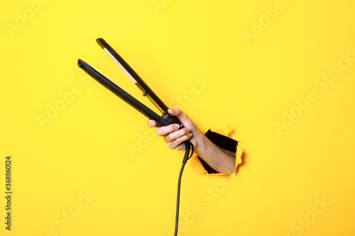 Female hand holds an electric curling iron with ceramic plates on a yellow backg Fototapete