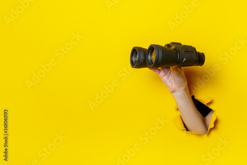 Obraz Female hand holds black binoculars on a yellow background. Looking through binoculars, journey, find and search concept - fototapety do salonu