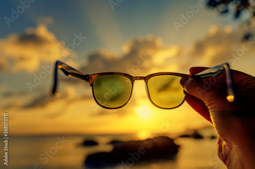 Fotografiet View of the sunset on the tropical sea through sunglasses in hand, abstract conc