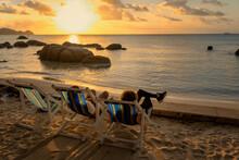 Two Girlfriends Sit On Beach C...