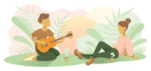 A Guy And A Woman Have A Romantic Evening With A Guitar And Some Hot Drinks. A Boy Is Singing And Playing Guitar For His Girlfriend. A Date In The Park.