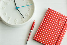 Notebook And Red Pen On Wooden White Table, White Style In Interior, Bussines And Planning, Red In White Polka Dots