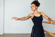 Young African American Woman Practicing Ballet Exercises Holding A Wooden Handrail