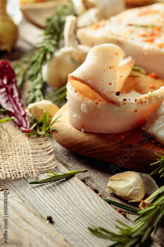 Fotografiet Lard with spices and herbs on a old wooden table.