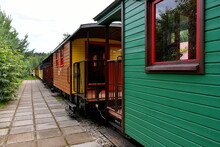 Close Up On A Set Of Colorful And Vivid Passenger Comparments Made Out Of Metal And Wood Standing On A Side Track Next To A Dense Forest Or Moor Seen On A Polish Countryside In Summer