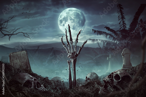 Zombie skeleton hand rising in dark Halloween night. Canvas Print