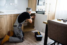 Full Length Shot Of Aged Repairman In Uniform Working, Fixing Kitchen Cabinet Using Screwdriver. Repair Service Concept