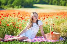 Beautiful Young Woman In White Dress Having Picnic In Poppy Field On A Summer Day