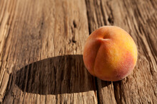 Ripe Juicy Fluffy Peach Or Nectarine On An Old Wooden Textured Board. Bright Sunlight Paints Shadow, Copy Space