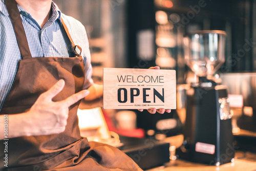 Fotografia Business owner attractive young Asian man in apron hanging we're open sign on front door  welcoming clients to new cafe