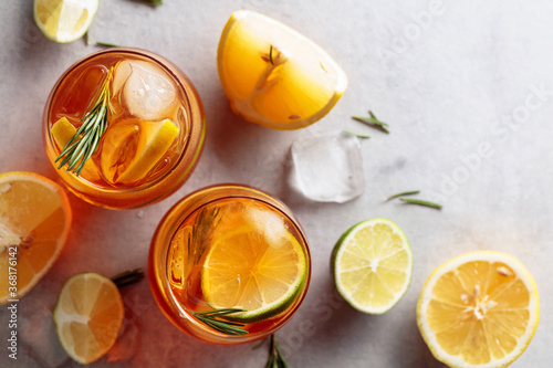 Obraz na plátně Traditional iced tea with lemon, lime and ice garnished with rosemary twigs