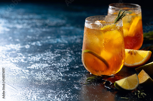 Fotografie, Obraz Traditional iced tea with lemon, lime and ice garnished with rosemary twigs