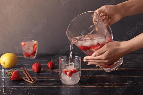 Obraz Woman pouring fresh strawberry lemonade in glass on table - fototapety do salonu
