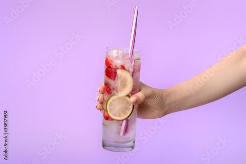 Obraz Hand with glass of fresh strawberry lemonade on color background - fototapety do salonu