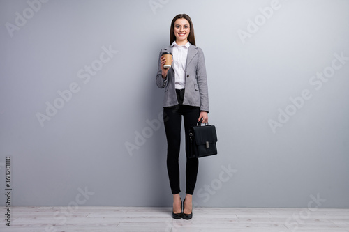 Obraz Full size photo of amazing pretty business lady young promoted chief hold diplomat takeout ht fresh coffee beverage wear specs shirt blazer pants high-heels isolated grey color background - fototapety do salonu
