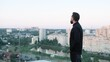 Businessman staying on a building roof and admiring the view, take a break from work.