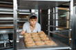 Close up of young caucasian woman baker is holding a tray with fresh bagels and looking to them at baking manufacture factory.