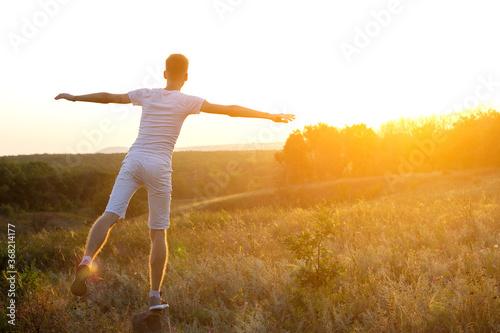 Young boy on the background of the departing sunset. Billede på lærred