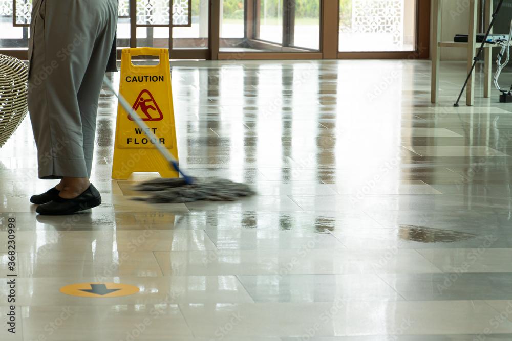 Fototapeta Mopping wet floor in lobby hotel. Background for caution wet floor.