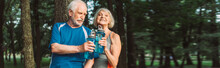 Panoramic Shot Of Smiling Senior Woman Holding Sports Bottle Near Husband In Park