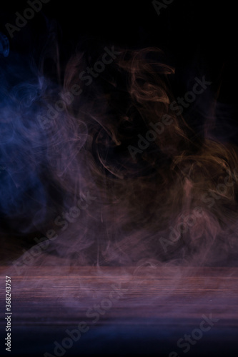 Canvas Print Conceptual image of multi-colored smoke isolated on dark black background and wooden table
