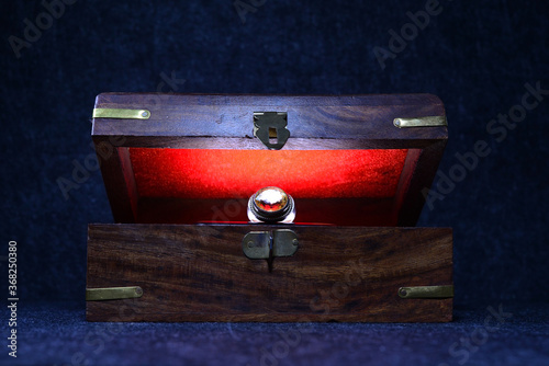 Платно Antique retro wooden box ajar with a jewellry ring and a red light inside it on