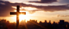 Silhouette Cross Against The Sky At Sunset. Dramatic City Background. Crucifixion Of Jesus Christ. Religion Concept.