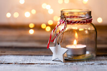 Idea For Simple Cozy Handmade Holiday Home Decor: Glass Jar With Candle Decorated With White Star And Red Ribbon. Christmas Lights, Wooden Background. Close Up, Macro, Copy Space For Text