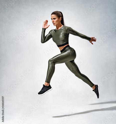 Obraz Sporty girl runner in silhouette. Photo of woman in sportswear on grey background. Strength and motivation. - fototapety do salonu