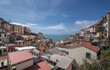 View of Riomaggiore village, first & most southern of Cinque Terre coastal villages, located in a small & narrow valley, as seen from east towards the Mediterranean sea, La Spezia, Liguria region, Ita