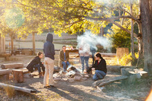 Group Of Young People Relaxing Around Campfire In Bushland On Sunny Winter Morning