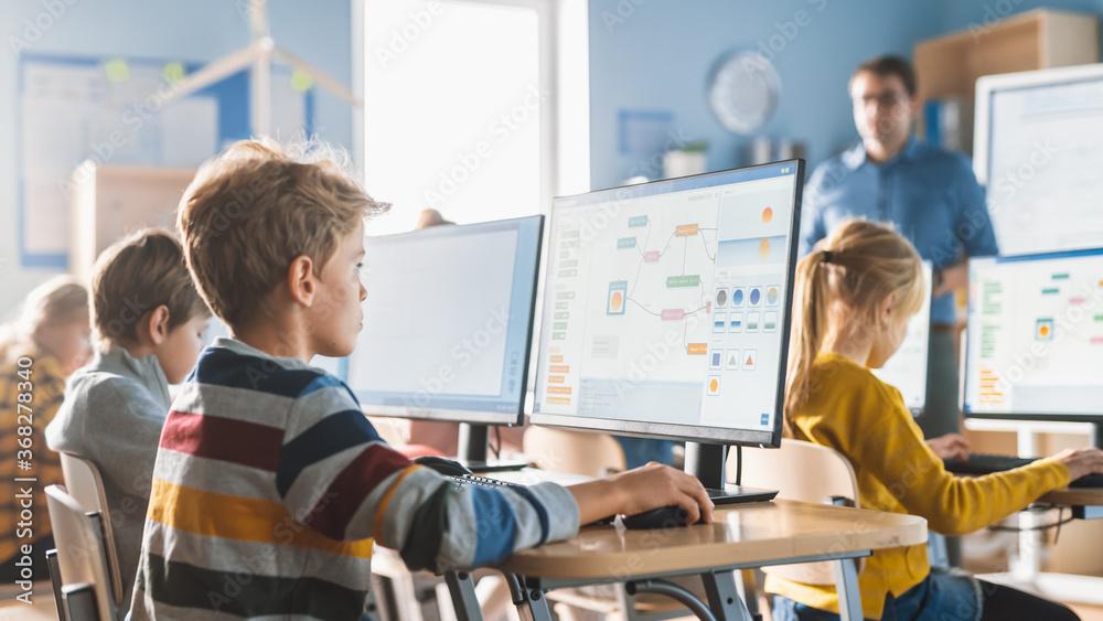 Fototapeta Elementary School Computer Science Classroom: Smart Little Schoolboy Work on Personal Computers, Learn Programming Language for Software Coding. Schoolchildren Getting Modern Education