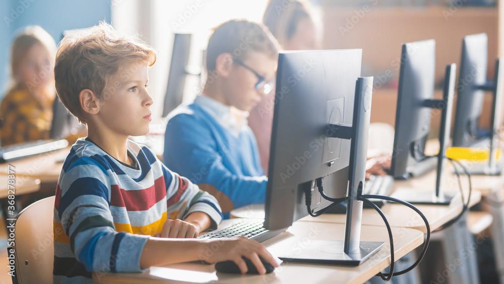 Fototapeta Elementary School Science Classroom: Smart Little Schoolchildren Sitting in Row and Work on Personal Computers, Learn Programming Language for Software Coding. Schoolchildren Getting Modern Education