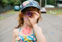 Girl Looking Through A Kaleidoscope