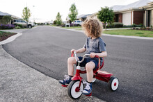 Child Riding A Red Tricycle On A Quiet Suburban Street At Sunset