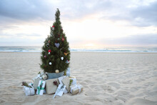 Decorated Christmas Tree On Beach At Sunrise With Present