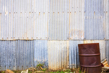Rusty Drum In Front Of Corrugated Iron Wall - Horizontal
