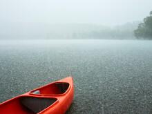 Red Canoe Sits Idle On Grey Ra...