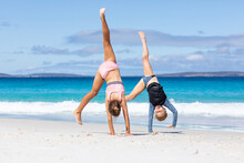 Two Little Girls Doing Cartwheels On The Beach