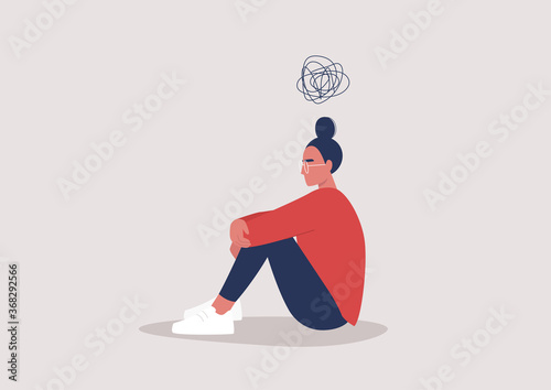 Obraz Young depressed female character sitting on the floor and holding their knees, a cartoon scribble above their head, mental health issues - fototapety do salonu