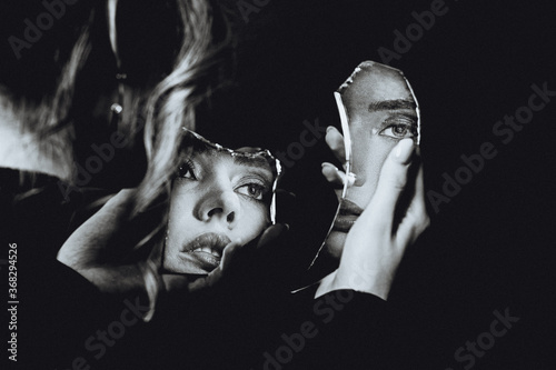Obraz na plátně Lovely woman looking at broken self-image mirror, black and white retro portrait